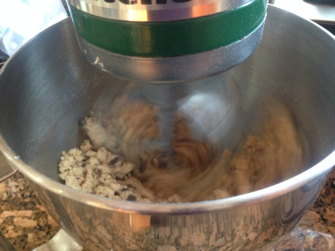 dough forming pea-sized clumps being mixed in green kitchenaid mixer