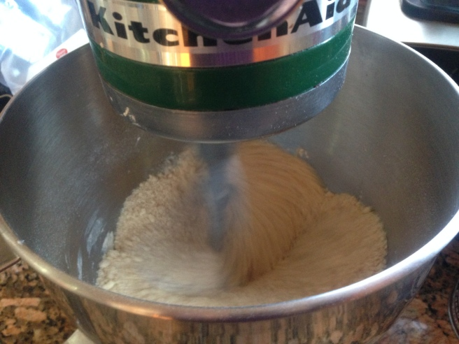 sandy mix of flour and butter being mixed in a green kitchenaid mixer