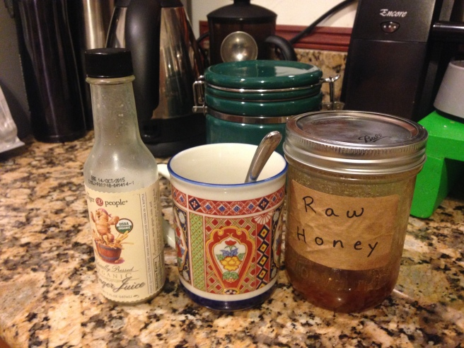 ginger juice, mug with spoon, and jar of honey