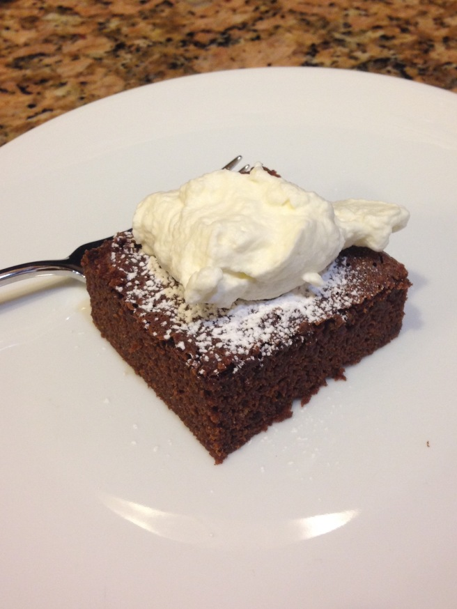 a square of chocolate cake topped with powdered sugar and whipped cream on a white plate