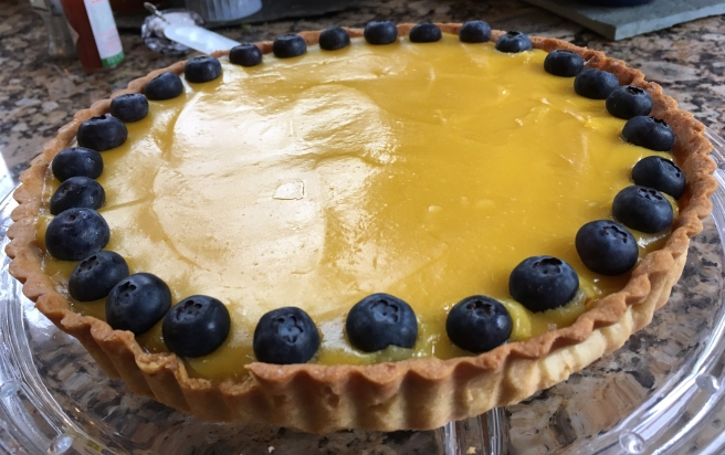 lemon tart with a rim of blueberries on a glass plate,